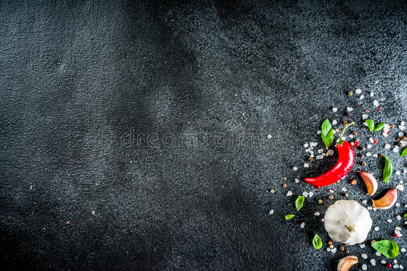 Cooking stone concrete background with spices. Cooking food stone concrete background with spices, olive oil, garlic, onion, pepper, herbs, basil. Top view copy royalty free stock photos