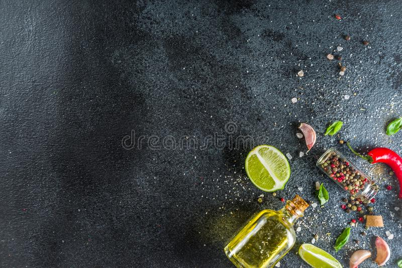Cooking stone concrete background with spices. Cooking food stone concrete background with spices, olive oil, garlic, onion, pepper, herbs, basil. Top view copy stock photos