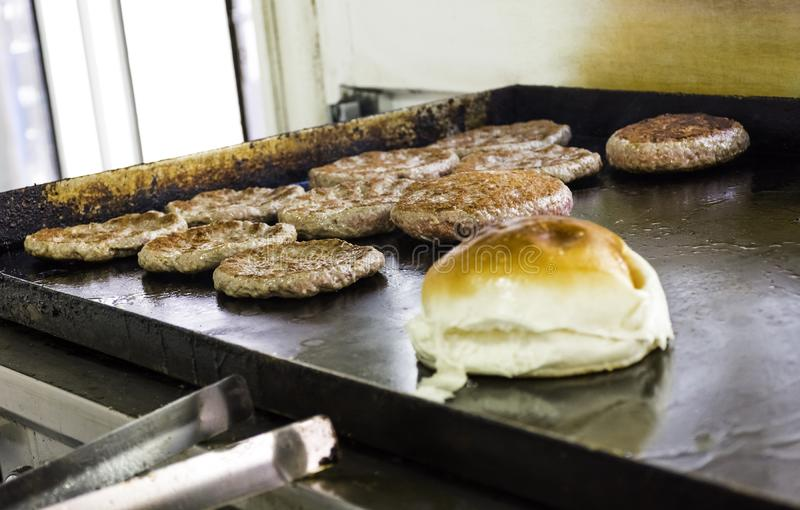 Cooking and Fraying Burgers and Hamburgers on Grill with Bread Loaf. stock image