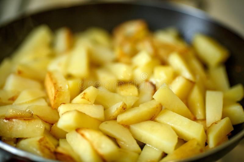 Cooking of fried potatoes or French fries in a frying pan royalty free stock images