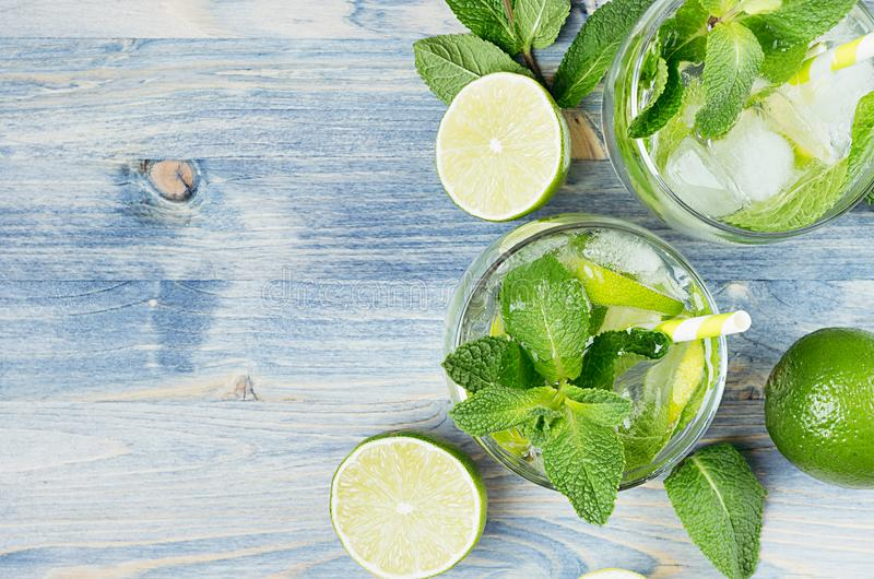 Cooking fresh cold summer beverage mojito with lime, leaf mint, straw, ice cubes, soda on blue wood background, top view, border. stock images