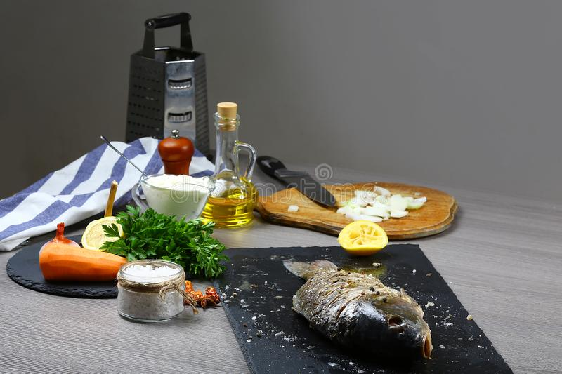 Cooking fresh fish carp, baking with Vegetables, lemon, herbs and spices on wooden table flat top view, copy text menu royalty free stock photo