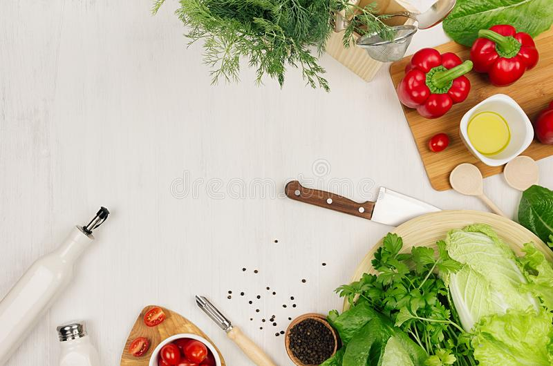 Cooking fresh raw spring salad of green and red vegetables, spices, oil with wooden kitchenware on white wooden background, border. Top view royalty free stock photos