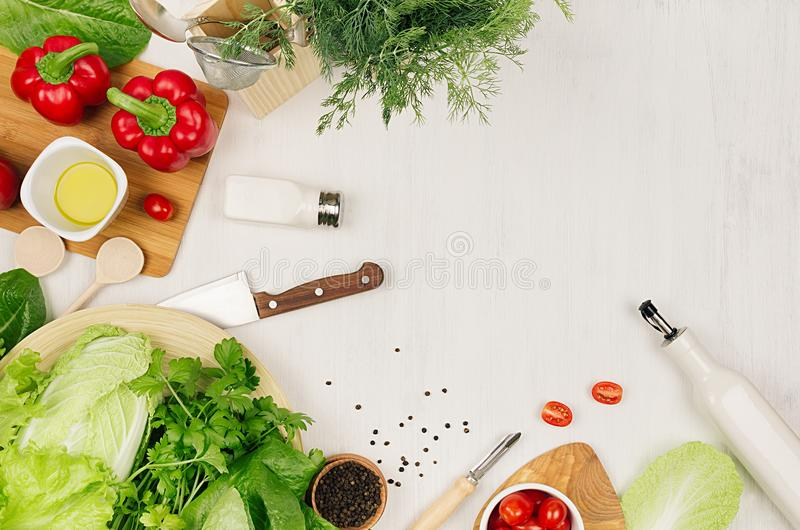 Cooking fresh raw spring salad of green and red vegetables, spices, oil with wooden kitchenware on white wooden background, border. Top view stock photo