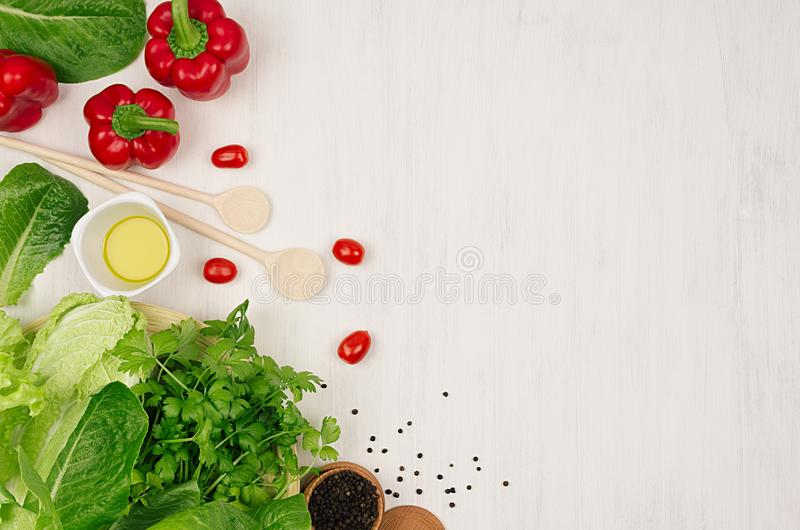 Cooking fresh spring salad of green and red vegetables, spices on white wooden background, border, top view. stock images