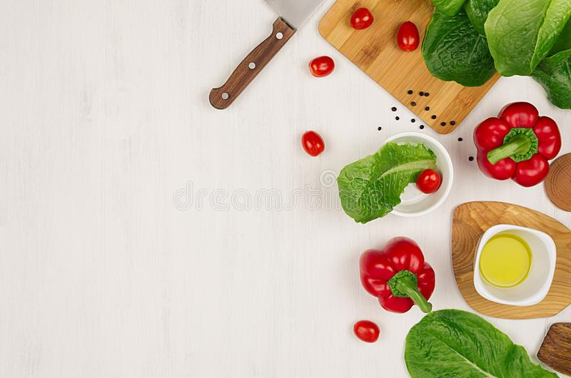 Cooking fresh spring salad of green and red vegetables, spices on white wooden background, border, top view. stock photos