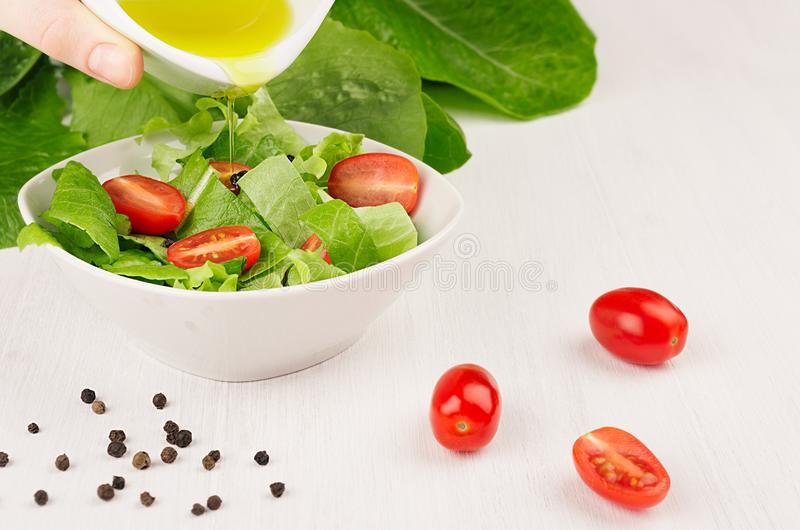 Cooking fresh spring salad of green spinach, cherry tomato slices. Hand holds bowl with olive oil, oil flow down on salad. royalty free stock photos