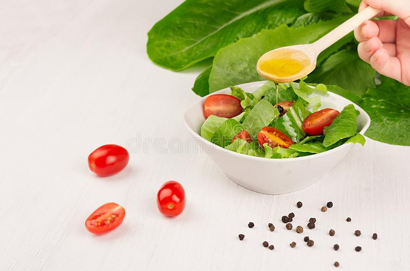 Cooking fresh spring salad of greens, cherry tomato slices on white wood background, copy space. Hand holds spoon and olive oil fl royalty free stock photos