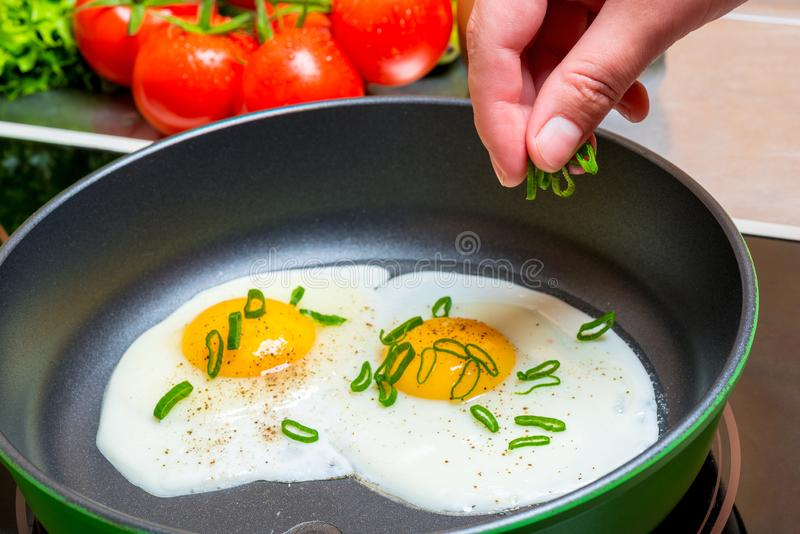 cooking fried scrambled eggs, hands with a wooden spatula royalty free stock images