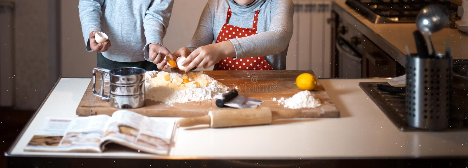 Cooking with fun at home. Banner with Two young chefs have fun at home preparing a cake or donut with eggs and flour stock images