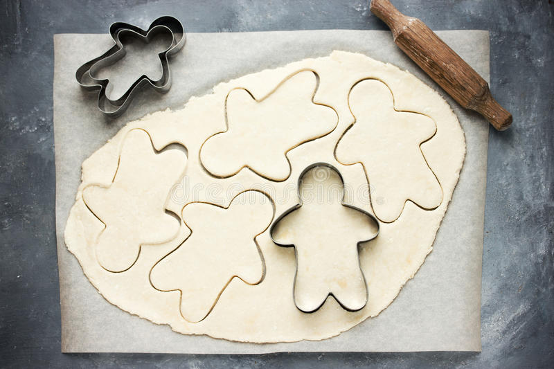 Cooking gingerbread man Christmas cookies. With raw dough metal cutter rolling pin - baking Christmas cookies stock photos