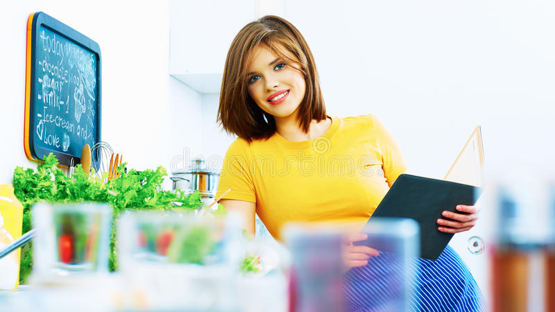 Cooking girl with recipe book. Beautiful smiling woman portrait in kitchen. Cooking girl with recipe book stock image