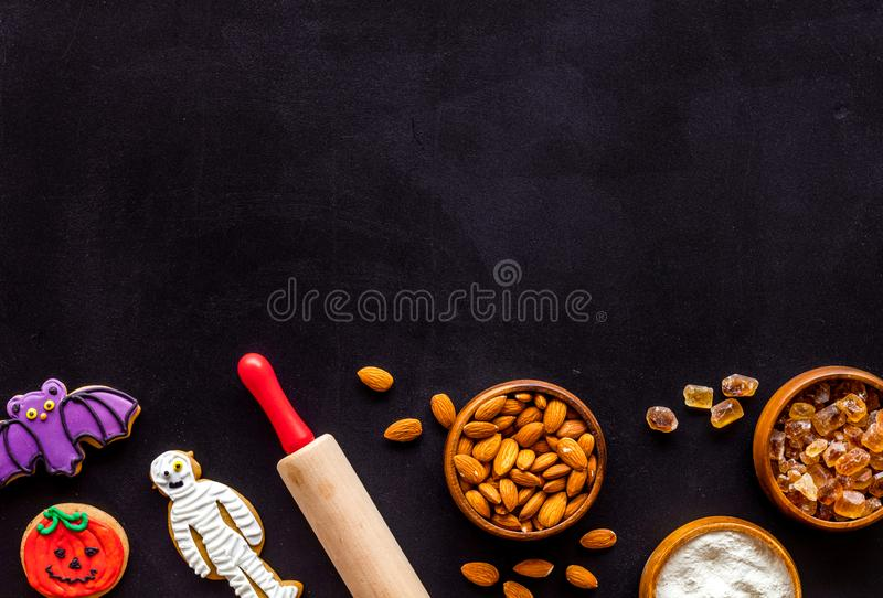 Cooking halloween cookies in shape of spooky figures, rollin pin, nuts and flour on black background top view mock up. Cooking halloween cookies in shape of stock photo