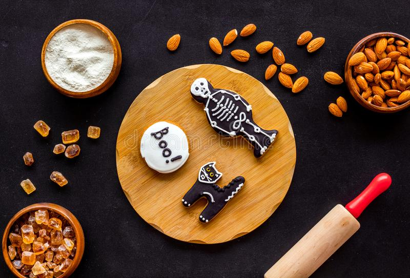 Cooking halloween cookies in shape of spooky figures, rollin pin, nuts and flour on black background top view. Cooking halloween cookies in shape of spooky stock photos