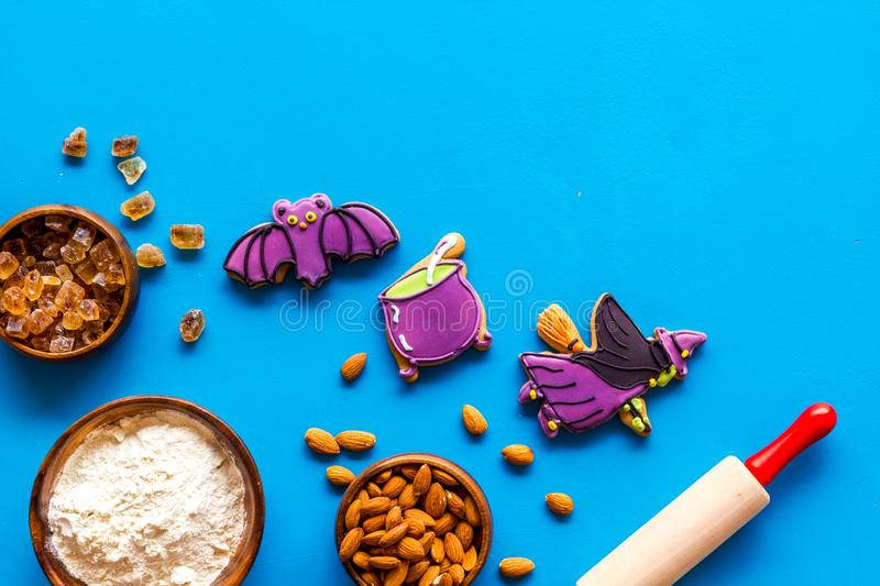 Cooking halloween cookies in shape of spooky figures, rollin pin, nuts and flour on blue background top view mockup. Cooking halloween cookies in shape of spooky royalty free stock photo