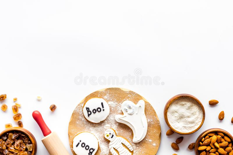 Cooking halloween cookies in shape of spooky figures, rollin pin, nuts and flour on white background top view mock up. Cooking halloween cookies in shape of stock photos