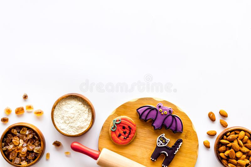 Cooking halloween cookies in shape of spooky figures, rollin pin, nuts and flour on white background top view mock up. Cooking halloween cookies in shape of royalty free stock photo