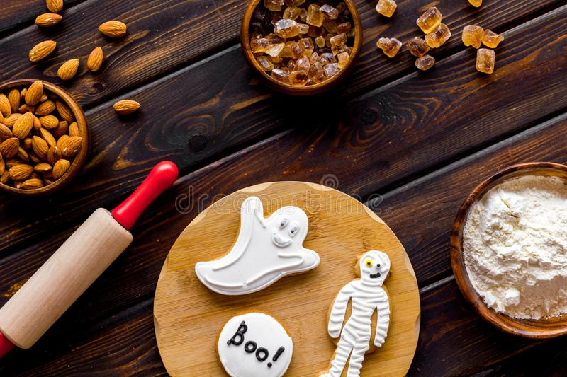 Cooking halloween cookies in shape of spooky figures, rollin pin, nuts and flour on wooden background top view. Cooking halloween cookies in shape of spooky royalty free stock photos