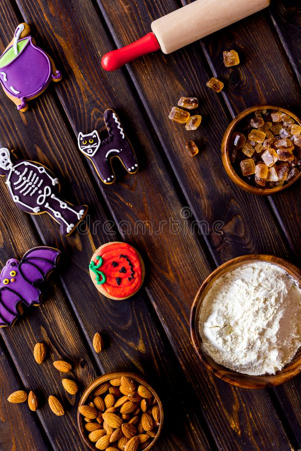 Cooking halloween cookies in shape of spooky figures, rollin pin, nuts and flour on wooden background top view. Cooking halloween cookies in shape of spooky royalty free stock images