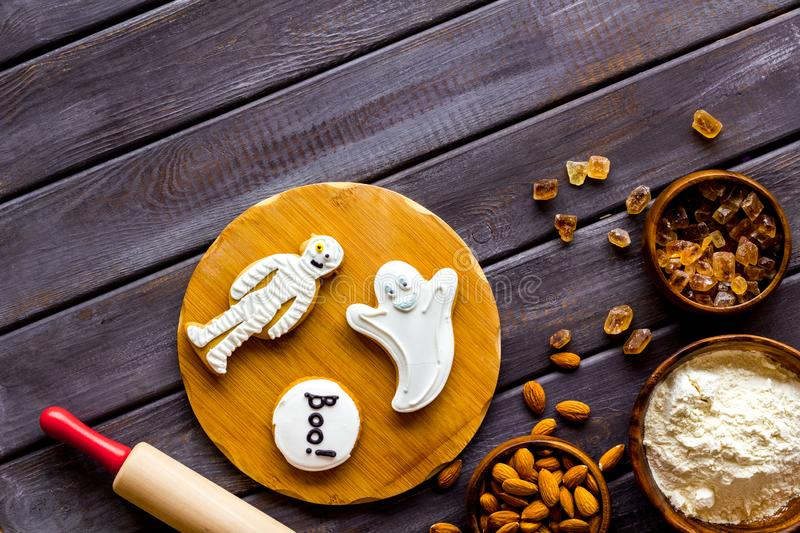 Cooking halloween cookies in shape of spooky figures, rollin pin, nuts and flour on wooden background top view mockup. Cooking halloween cookies in shape of royalty free stock images