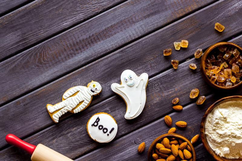 Cooking halloween cookies in shape of spooky figures, rollin pin, nuts and flour on wooden background top view mockup. Cooking halloween cookies in shape of stock photo