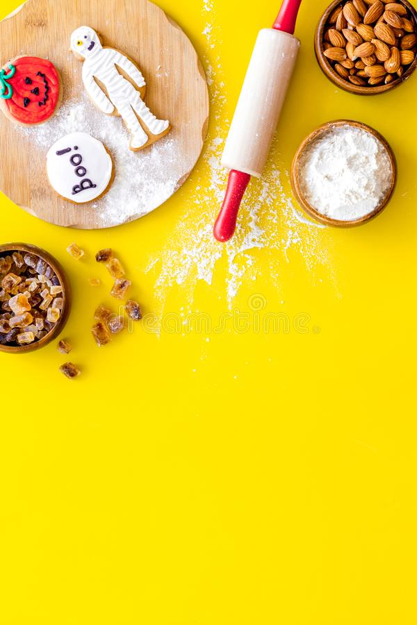 Cooking halloween cookies in shape of spooky figures, rollin pin, nuts and flour on yellow background top view copyspace. Cooking halloween cookies in shape of stock image