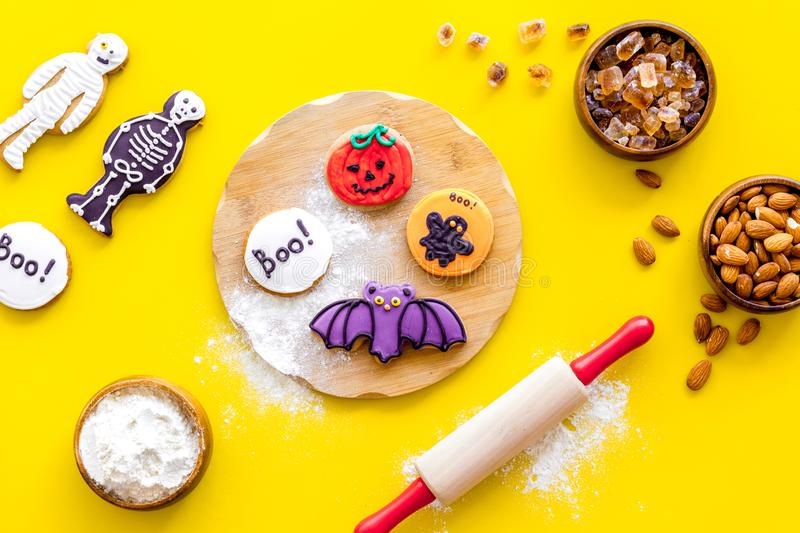 Cooking halloween cookies in shape of spooky figures, rollin pin, nuts and flour on yellow background top view. Cooking halloween cookies in shape of spooky royalty free stock photos
