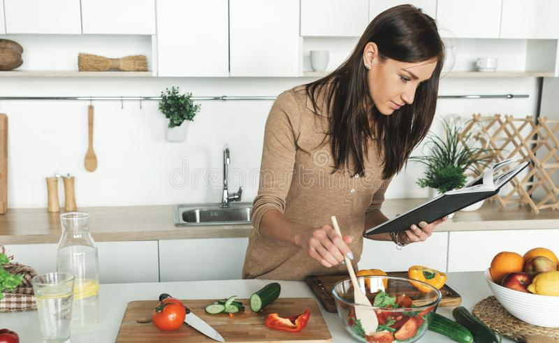 Cooking healthy food home kitchen Beautiful young woman preparing summer salad stock image