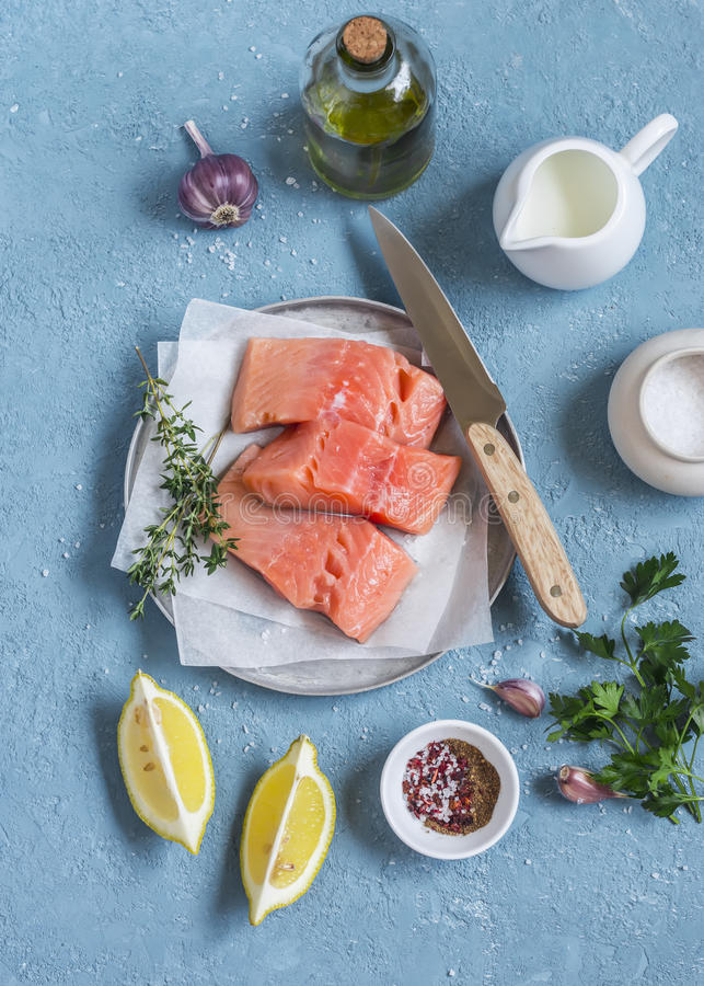Cooking healthy lunch - raw salmon, lemon, olive oil, spices and herbs on a blue background. stock photo