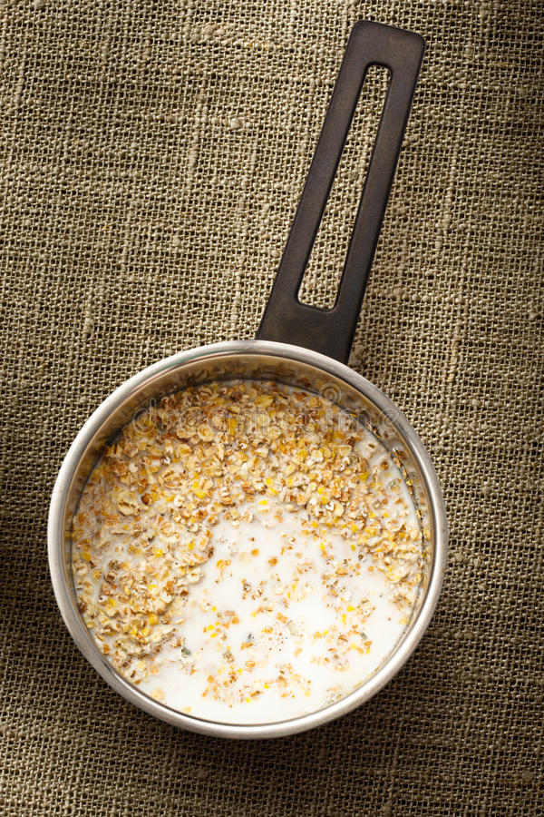 Cooking healthy porridge in metal pot royalty free stock images