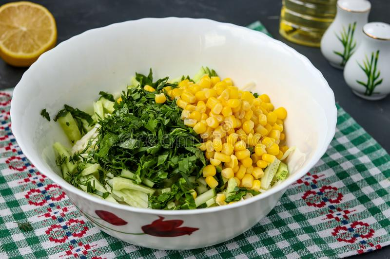 Cooking healthy salad with cabbage, cucumbers and corn, horizontal photo, slicing parsley into a salad stock image
