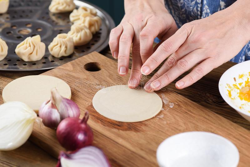 Cooking healthy vegetarian dish. Woman hands making steam dumplings momo royalty free stock photography