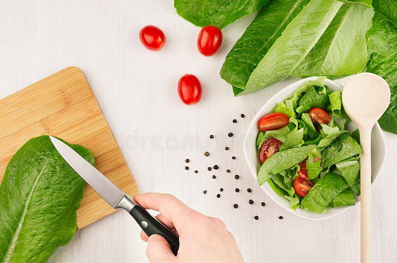 Cooking healthy vegetarian spring salad - fresh greens, tomatoes, pepper and hand with knife on white wood background, top view. stock photos