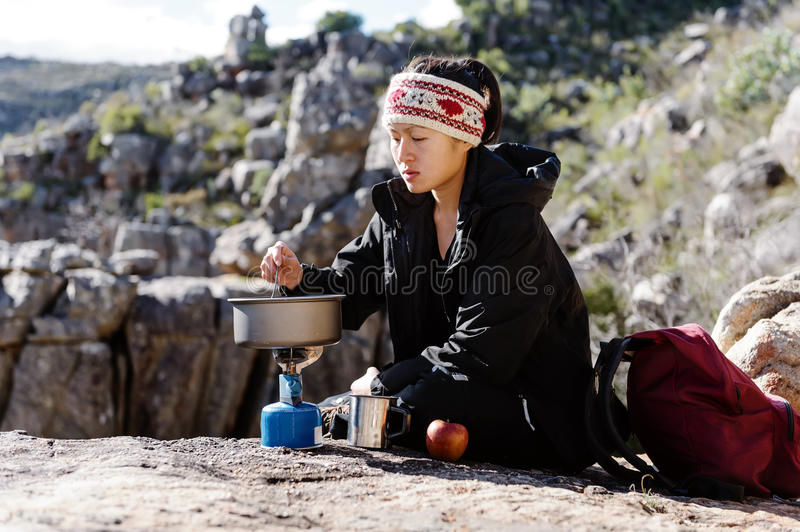 Cooking hiker woman. Portrait of an asian chinese backpacker cooking on a camping gas stove while hiking and exploring on a tourist adventure in the wilderness royalty free stock photography