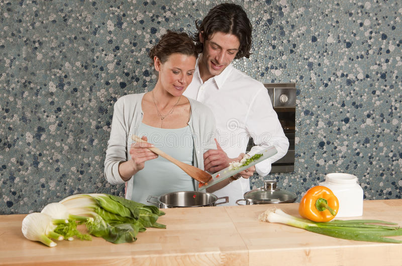 Cooking he holds her arm