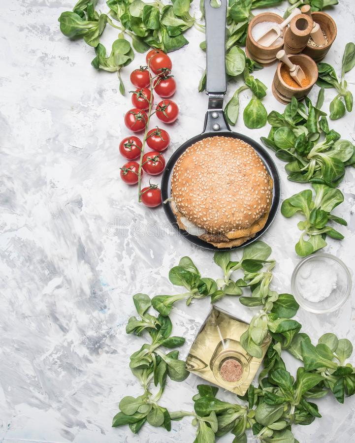 Cooking a homemade burger with chicken cutlet, and a side dish of salad with cherry tomatoes, seasonings and oil, on white rusti royalty free stock image
