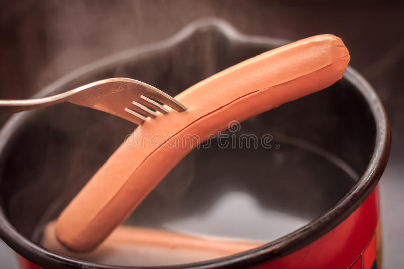 Cooking hot dogs in pot stock images