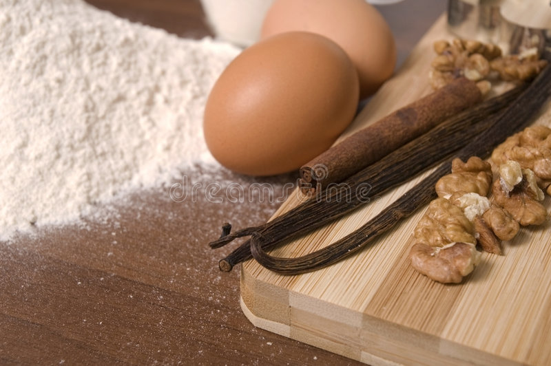 Cooking ingredients. Flour, eggs, sugar, spices - cinnamon, vanilla and nuts stock images