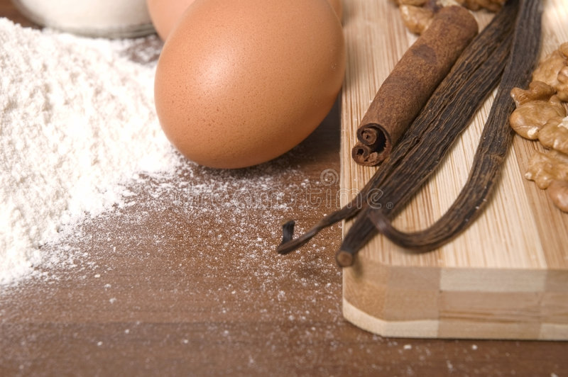 Cooking ingredients. Flour, eggs, sugar, spices - cinnamon, vanilla and nuts stock photography