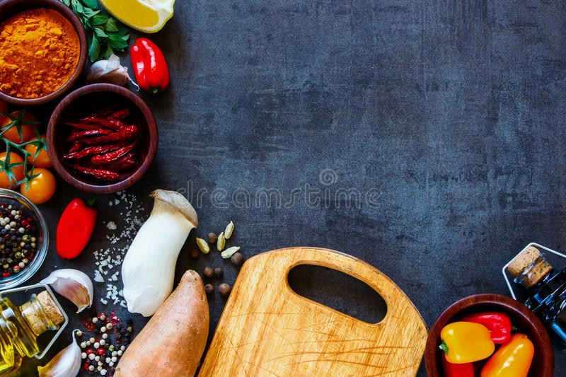 Cooking ingredients background. Healthy colorful farm vegetables and ingredients for tasty cooking on rustic background with space for text, border, top view royalty free stock photo