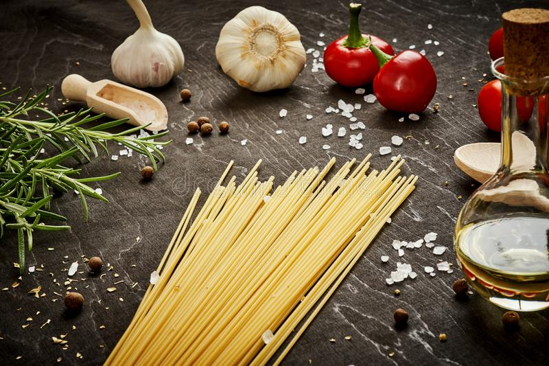 Tomatoes garlic salt olive peppers and pasta on a black table royalty free stock photo