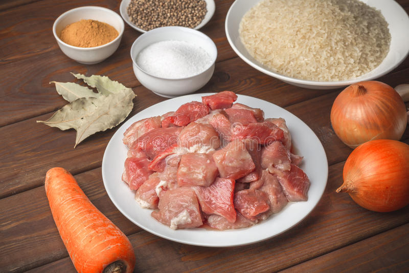 Cooking ingredients. Sliced raw meat, rice, spices, garlic, carrot, onion, bay stock images