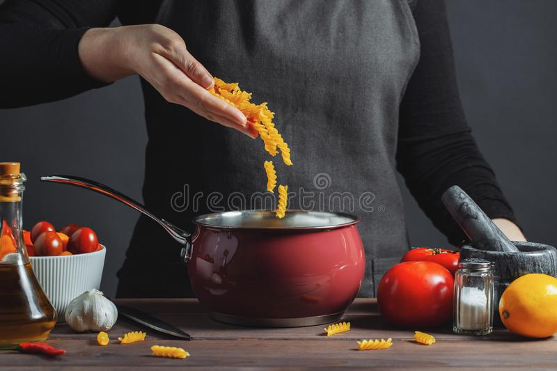 Cooking italian pasta in a pot in the kitchen, Chef preparing food, meal. The woman-the cook throws into the pot the pasta fusilli royalty free stock photo