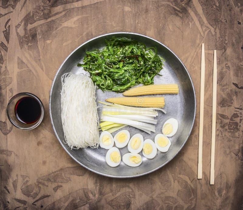 Cooking Korean food, glass noodles, chuka seaweed, boiled quail eggs, ginger, corn pan and chopsticks stock image