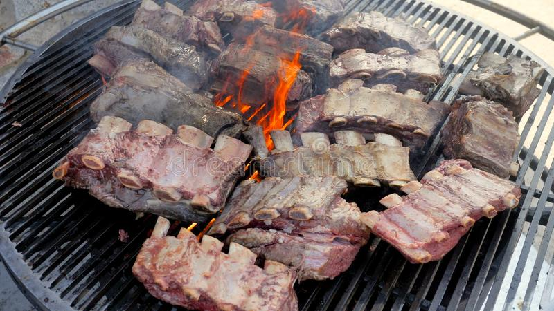 Cooking large juicy pieces of raw fatty natural marinated pork meat beef calves on a griddle grill. American barbecue in. Town for a big company in honor of stock image