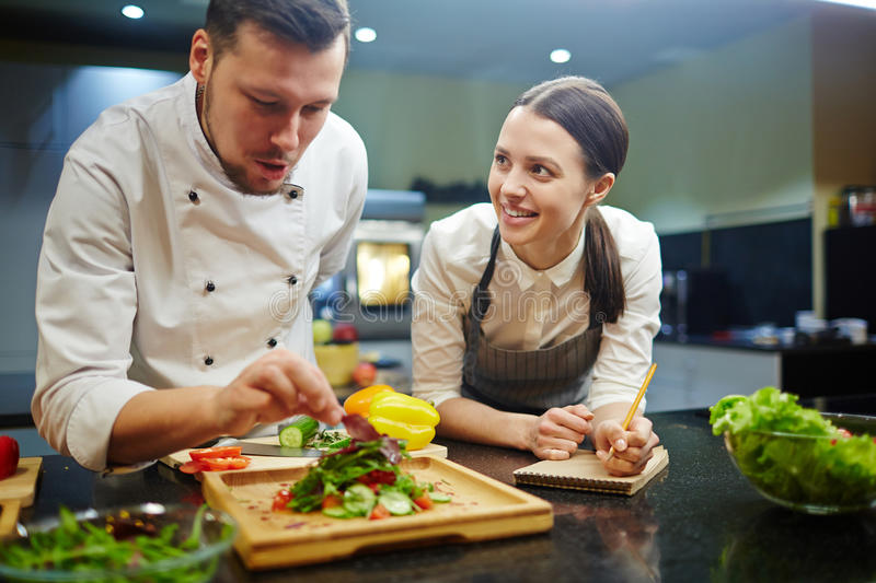 Cooking lesson. Young women writing down recipe of vegetable salad while chief cooking it royalty free stock photo
