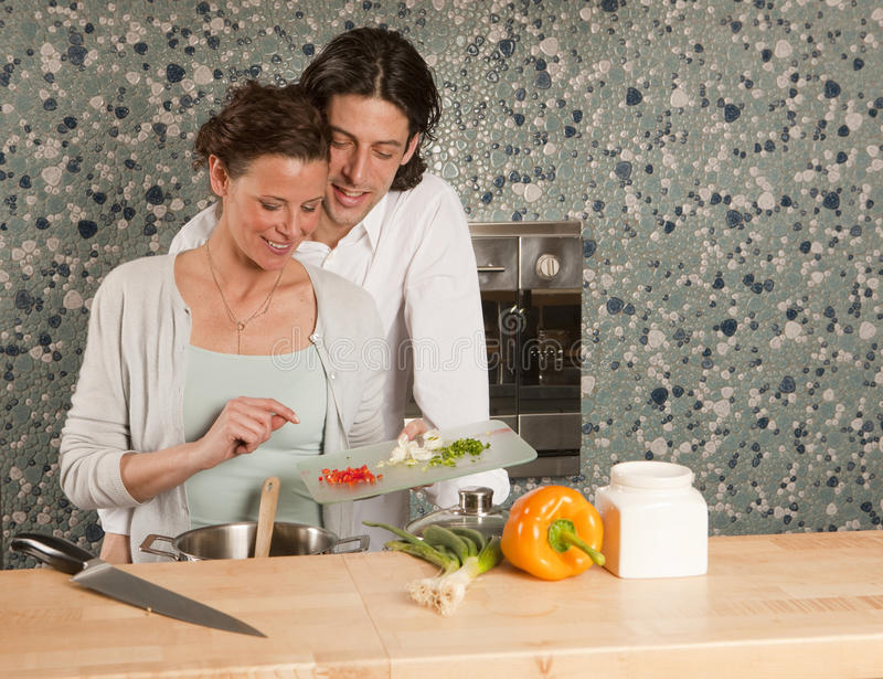 Download Cooking He Looks Over Her Shoulder Stock Image - Image of cheerfulness, facial: 10552681