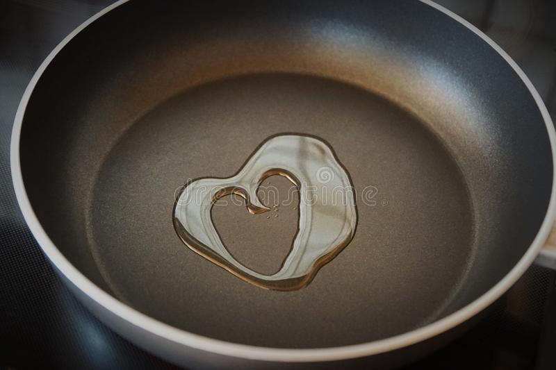 Cooking with love. Oil in the shape of a heart in a pan