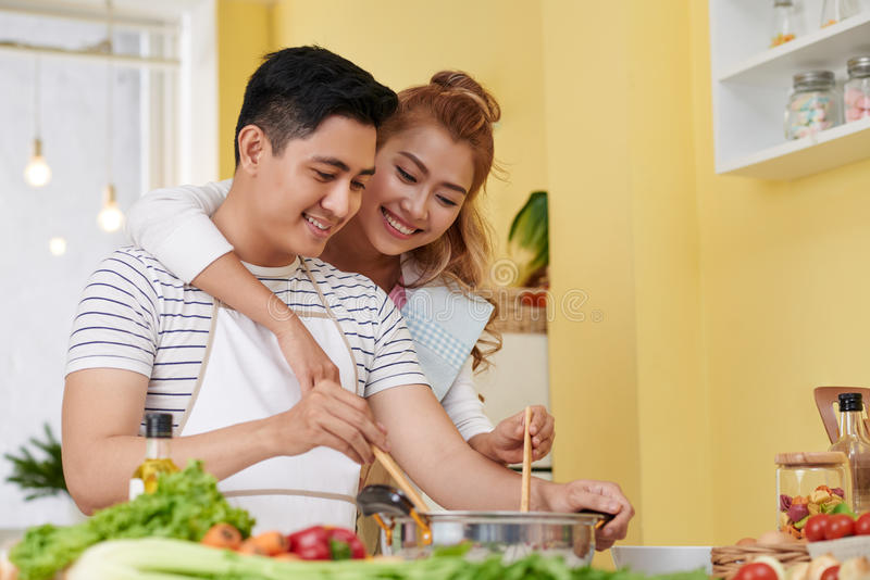 Cooking with love. Young Vietnamese couple in love cooking together stock images