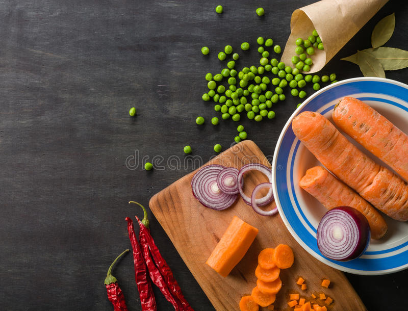 Cooking a meal of fresh vegetables. The composition on a dark wooden background. royalty free stock images